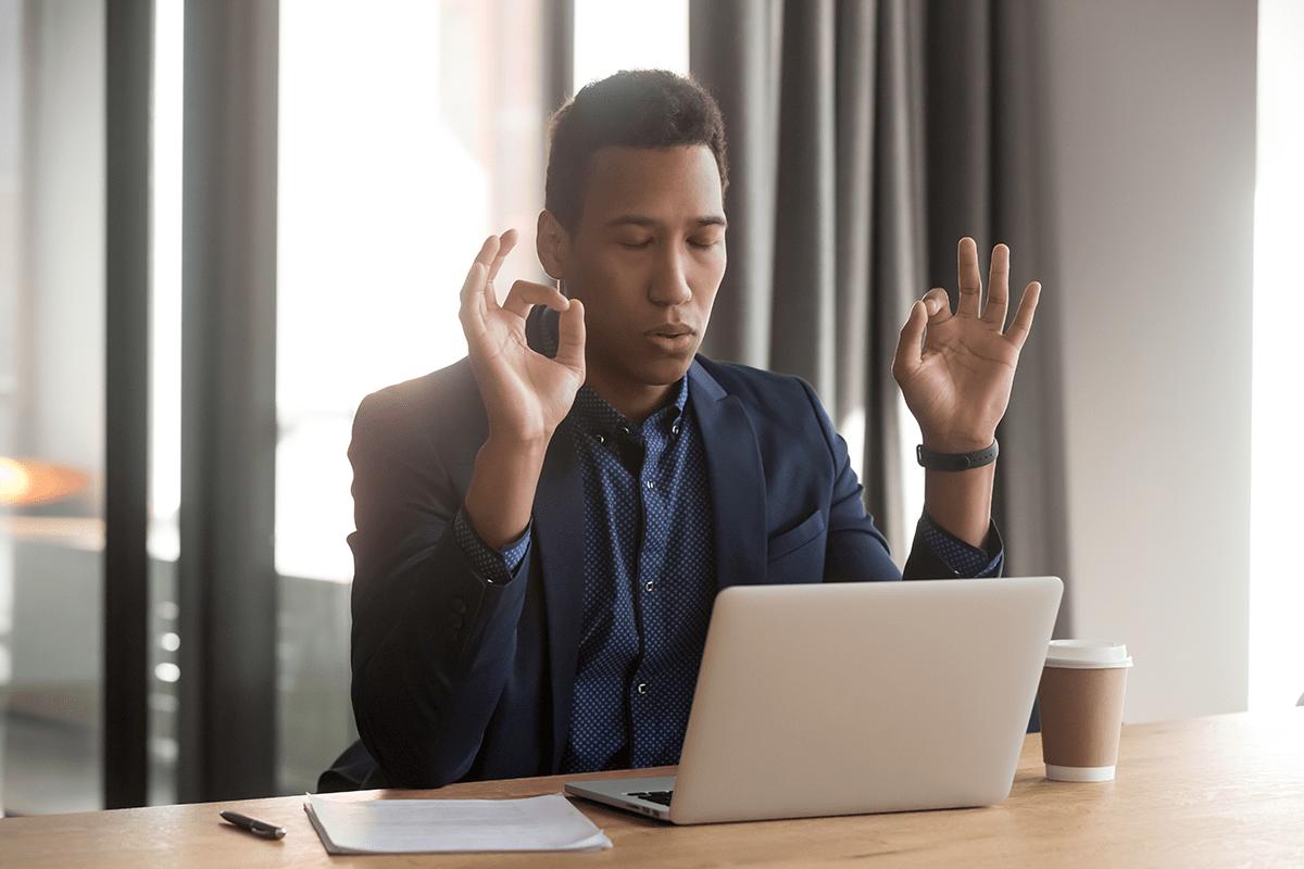 man sitting at laptop meditating with eyes closed