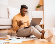 person sitting on floor with laptop celebrating with air punch